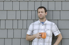 Young man enjoying a hot beverage alone outside. Royalty Free Stock Images