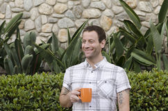 Young man enjoying a hot beverage alone outside. Stock Photos