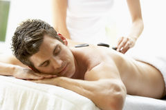 Young Man Enjoying Hot Stone Treatment Royalty Free Stock Images