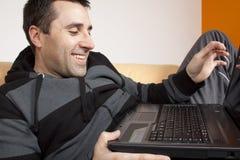 young man Enjoying laptop at home Stock Photo