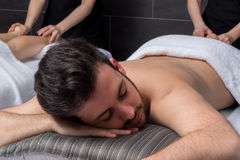 Young man enjoying massage with girlfriend. Close up portrait of young man at massage session in spa Royalty Free Stock Photos