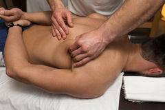 Young Man Enjoying A Massage. Masseur Doing Massage On Man Body In The Spa Salon Stock Images