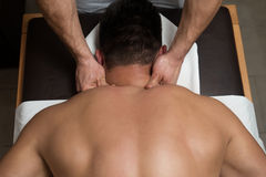 Young Man Enjoying A Massage. Masseur Doing Massage On Man Body In The Spa Salon Royalty Free Stock Photo