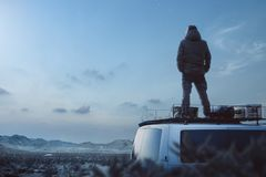 Young man enjoying a moonlit night on top of his camper van. A man is standing on the roof of a camper van, hands in his pockets. He is enjoying the tranquil royalty free stock photography