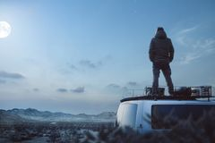 Young man enjoying a moonlit night on top of his camper van. A man is standing on the roof of a camper van, hands in his pockets. He is enjoying the tranquil royalty free stock images