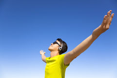 Young man enjoying music  with blue sky background Royalty Free Stock Photo