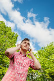Young man enjoying music out in the park Stock Photo