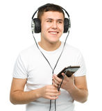 Young man enjoying music using headphones Stock Images