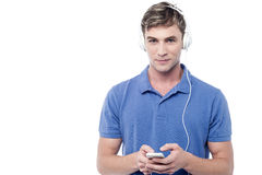 Young man enjoying music and using his mobile Royalty Free Stock Images