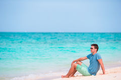Young man enjoying the music on white beach Stock Photo