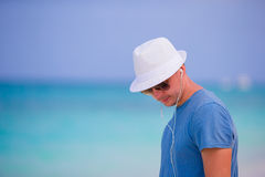 Young man enjoying the music on white sandy beach. Happy tourist relaxing on summer tropical vacation. Stock Photos