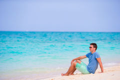 Young man enjoying the music on white sandy beach. Happy tourist relaxing on summer tropical vacation. Royalty Free Stock Photography