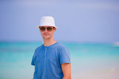 Young man enjoying the music on white sandy beach. Happy tourist relaxing on summer tropical vacation. Young beautiful man listening to music on white beach Royalty Free Stock Image