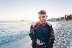 Young man enjoying the music on white sandy beach. Happy tourist relaxing on vacation. Royalty Free Stock Image