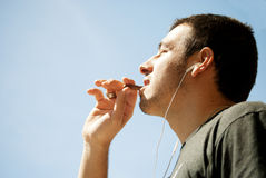 Chocolate dream. Young man enjoying a piece of his chocolate in the sunshine while listening to music Stock Image