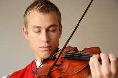 Young man enjoying playing violin. Young blond man in folkloric costume playing violin with closed eyes Stock Photos
