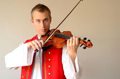 Young man enjoying playing violin. Young blond man in folkloric costume playing violin Stock Photos
