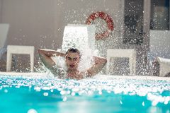 Young man enjoying  pool spa day in relaxing vacation resort.Pampered man,metro sexual,caring for body and well being. Hydro massage for neck pain.Relaxing Stock Image