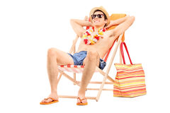 Young man enjoying seated in a sun lounger Royalty Free Stock Image