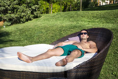 Young man  enjoying the summer vacation laying on sunbed in a tropical garden Royalty Free Stock Photos