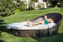Young man  enjoying the summer vacation laying on sunbed in a tropical garden Royalty Free Stock Images