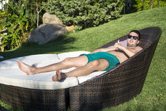 Young man  enjoying the summer vacation laying on sunbed in a tropical garden Royalty Free Stock Image