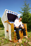 Young man enjoying the sun leaning on a wicker chair. Under a beutiful sunny day Royalty Free Stock Photos