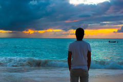 Young man enjoying sunset during beach vacation Royalty Free Stock Images