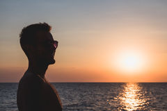 Young man enjoying sunset by the sea Royalty Free Stock Photography