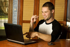 Young man enjoying surfing the web. Inside home Stock Photos