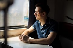 Young man enjoying train travel - leaving his car at home, looks out of window, has time to admire landscape. Passing by royalty free stock images