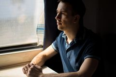 Young man enjoying train travel - leaving his car at home, looks out of window, has time to admire landscape. Passing by stock photo