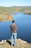 Young man enjoying the view of a beautiful lake. Young man looking and enjoying the view of a beautiful lake Royalty Free Stock Images