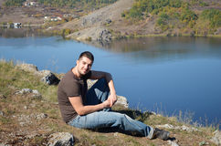 Young man enjoying the view of a beautiful lake. Young man relaxing and  enjoying the view of a beautiful lake Royalty Free Stock Image