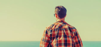 Young man enjoying view of sea. Rear view. Image with instagram filter Royalty Free Stock Image