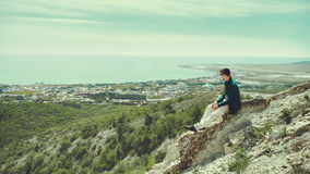 Young man enjoying view of sea in summer. Young man sitting on peak of mountain and enjoying view of sea in summer Royalty Free Stock Photo