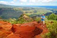 Young man enjoying a view into Waimea Canyon. Young man enjoying stunning view into Waimea Canyon, Kauai, Hawaii Stock Photo