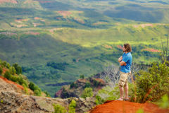 Young man enjoying a view into Waimea Canyon. Young man enjoying stunning view into Waimea Canyon, Kauai, Hawaii Royalty Free Stock Photography