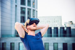 Young man enjoying virtual reality glasses headset or 3d spectacles looking up and standing against modern building background out Stock Photo