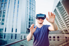 Young man enjoying virtual reality glasses headset or 3d spectacles standing against modern city building background outdoors. Tec Royalty Free Stock Photography