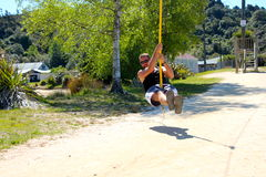 Young man enjoying a zipline in the golden bay Royalty Free Stock Photo