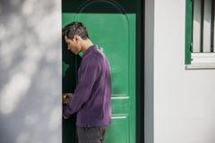 Young man entering a door in an exterior wall of a Stock Photos