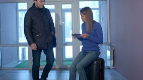 Young man entering the doors and talking to smiling woman with tablet sitting on suitcase. Professional shot in 4K resolution. 073. You can use it e.g. in your stock footage