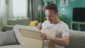 Young man enters his living room with cardboard parcel and open it