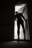 Young man enters opening door from dark. Room and looks inside to the light Stock Images