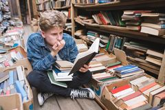 Young man with enthusiasm reads an interesting book sitting on the floor in the old library stock images