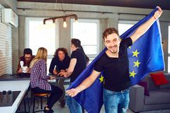 Young man with the european flag in his hands  in the room. Young men with the european flag in his hands on the background of friends in the room Royalty Free Stock Photo