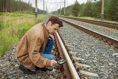 Young man examines the rail surface Royalty Free Stock Photography
