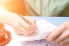 A young man examines and signs the letter. The concept of correspondence. royalty free stock image