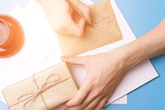 A young man examines and signs the letter. The concept of correspondence. A young man examines and signs the letter. The concept of correspondence royalty free stock photography